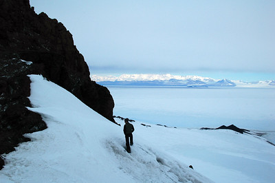 CASTLE ROCK, ROSS ISLAND, ANTARCTICA: Tony explores further beyond the ridge while the sun glimmers off the Convoy Range of mountains on the mainland of Antarctica.
